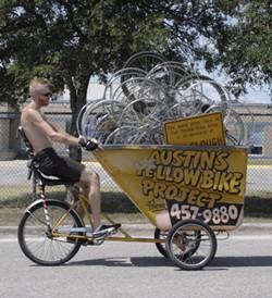 A loyal volunteer moves bike parts to the new YBP facility